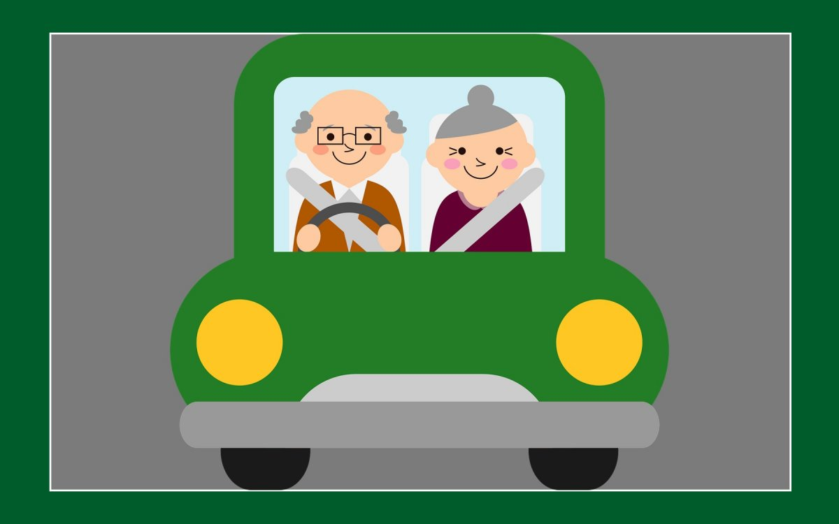 smiling grey-haired man and woman in a green car