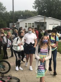 Students wearing face masks walking into school